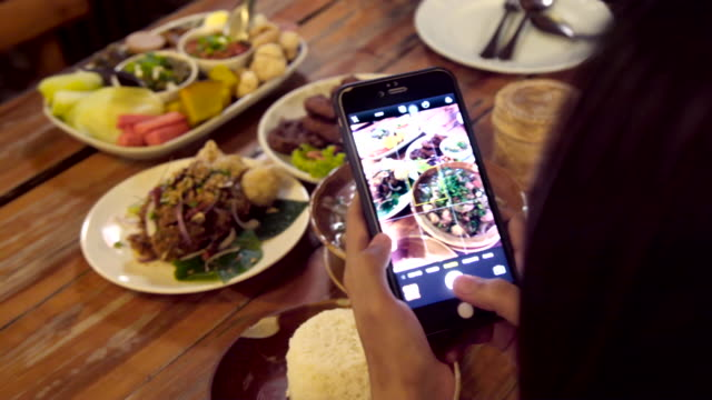 asian woman using mobile smart phone taking photo group of thai foods. - foodie stock videos & royalty-free footage