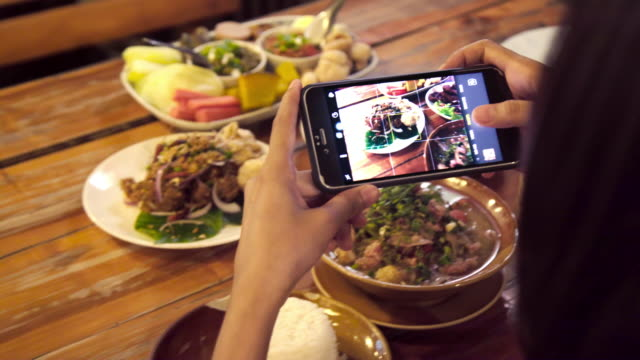 asian woman using mobile smart phone taking photo group of thai foods. - food photography stock videos & royalty-free footage