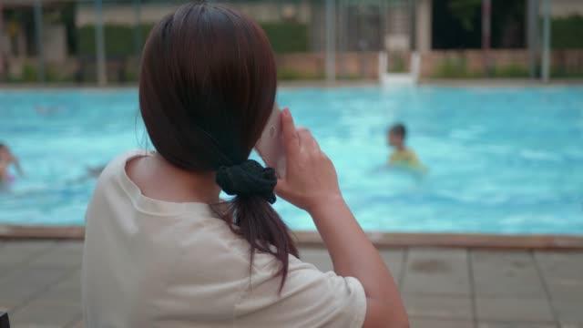 asiatisk kvinna med hjälp av mobil smart telefon textning meddelanden vid poolen. - utebassäng bildbanksvideor och videomaterial från bakom kulisserna