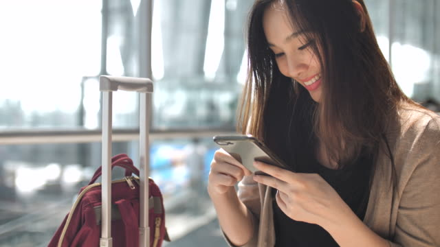 asian woman using on smart phone while waiting for her flight - business travel stock videos & royalty-free footage