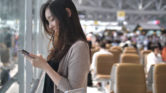 asian woman using on smart phone while waiting for her flight - biglietto aereo video stock e b–roll