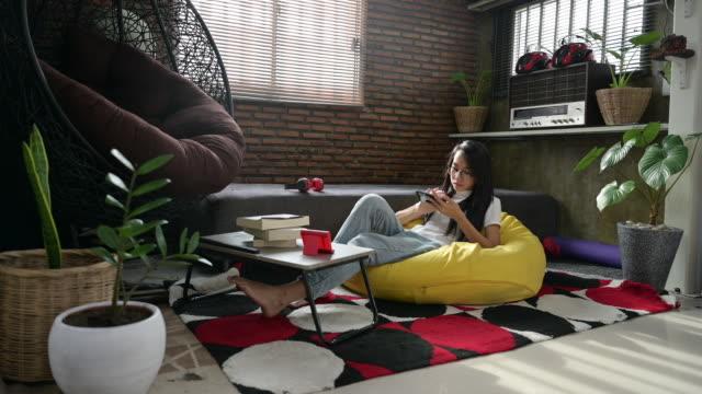 vídeos y material grabado en eventos de stock de mujer asiática usando el teléfono y relajarse en la sala de estar - cabello largo