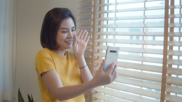 asian woman using phone, asia girl chatting with a friend through a video call at her home - conference phone stock videos & royalty-free footage