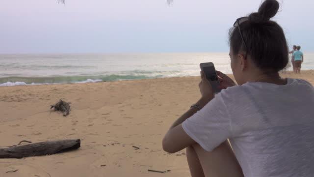 4K: Asian Woman using phone at the beach