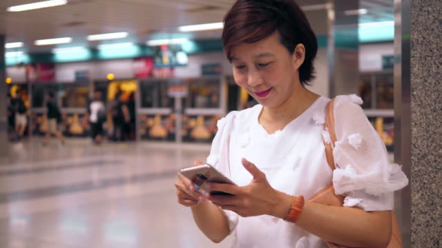 Asiatische Frau mit Telefon in U-Bahn