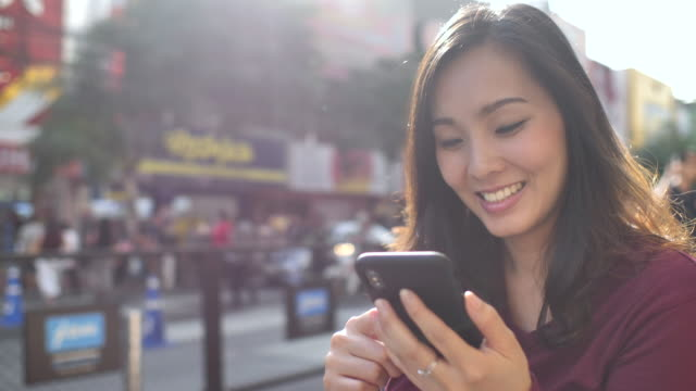 asian woman using phone in the city with sunset - text messaging stock videos & royalty-free footage