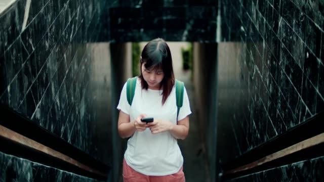 asiatische frau mit telefon im öffentlichen park - connection in process stock-videos und b-roll-filmmaterial