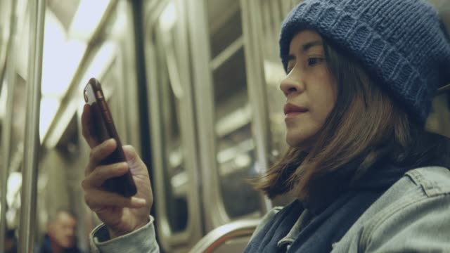 asian woman using phone on subway in new york - subway train stock videos & royalty-free footage
