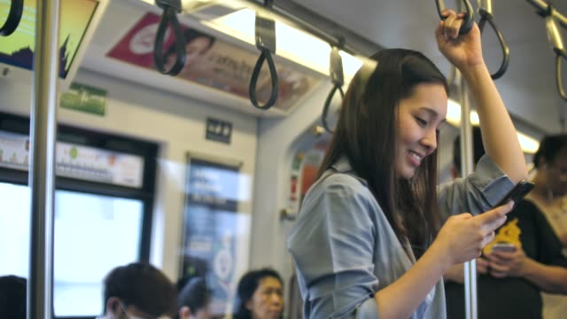 asian woman using phone on train - underground rail stock videos and b-roll footage