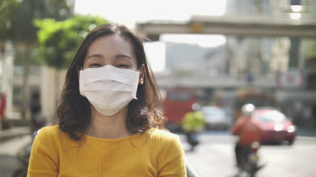 asian woman using pollution mask for protection from air pollution in big city - activity stock videos & royalty-free footage