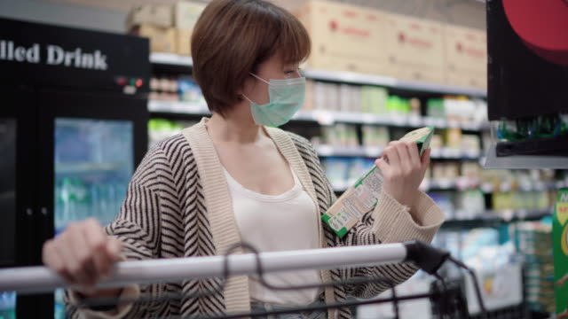 asian woman using pollution mask for shopping cart in supermarket - market retail space stock videos & royalty-free footage