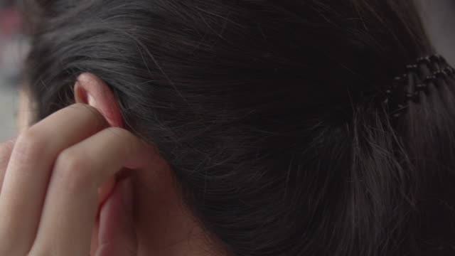 Asian woman using smart mobile and itching on her ear