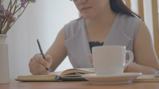 スマートフォンを使い、ホームオフィスでメモを書くアジアの女性。 - ノート点の映像素材/bロール