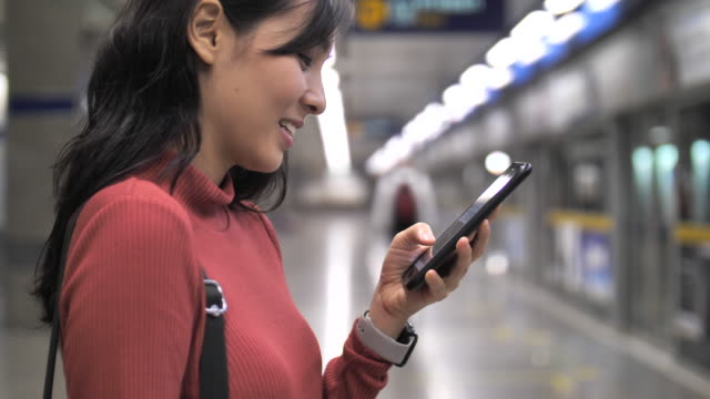 asian woman using smart phone at metro station - arts culture and entertainment stock videos & royalty-free footage