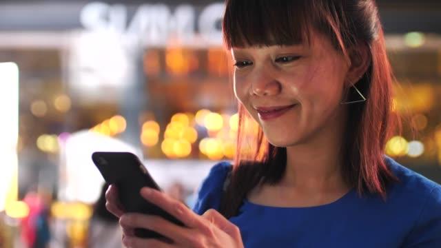 vídeos de stock, filmes e b-roll de mulher asiática que usa o telefone esperto na noite - formulário de aplicação