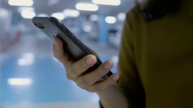 vidéos et rushes de femme asiatique à l'aide de téléphone intelligent sur le parking - 25 29 ans