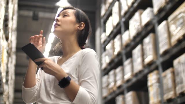 アジアの女性のスマートフォンチェックリストを使用して倉庫、注文の出荷 - 製造所点の映像素材/bロール