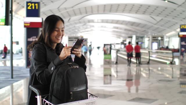 Asian Woman Using Smart Phone in Airport Terminal, Departure Area