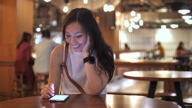 asian woman using smart phone in cafe - black hair stock videos & royalty-free footage