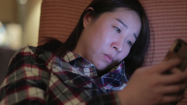 asian woman using smart phone in sofa - chinaface stock videos & royalty-free footage