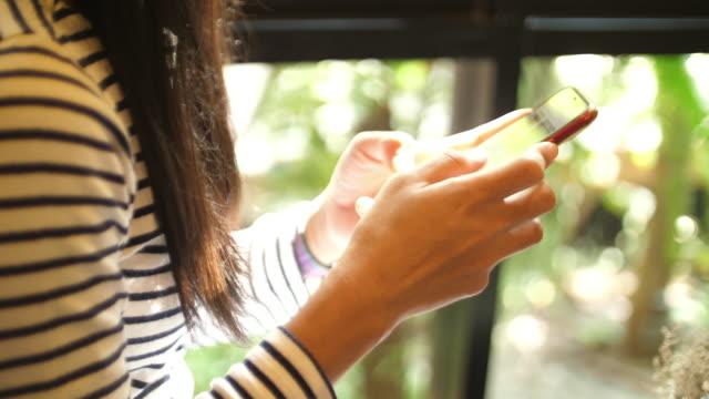 asiatisk kvinna som använder smart telefon i caféet - kvinnor i 30 årsåldern bildbanksvideor och videomaterial från bakom kulisserna
