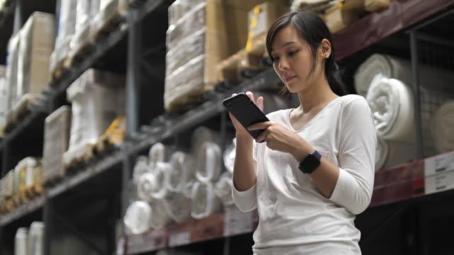 倉庫でスマートフォンを使用してアジアの女性 - 商品点の映像素材/bロール