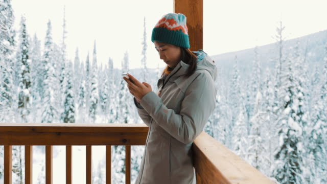 asian woman using smart phone in winter - chinaface stock videos & royalty-free footage