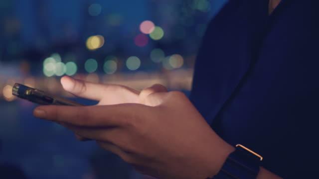 asiatische frau mit smartphone spät in der nacht. - interaktivität stock-videos und b-roll-filmmaterial