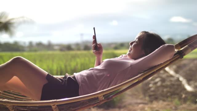vídeos y material grabado en eventos de stock de mujer asiática usando el teléfono inteligente acostado en la hamaca en el atardecer - casual clothing