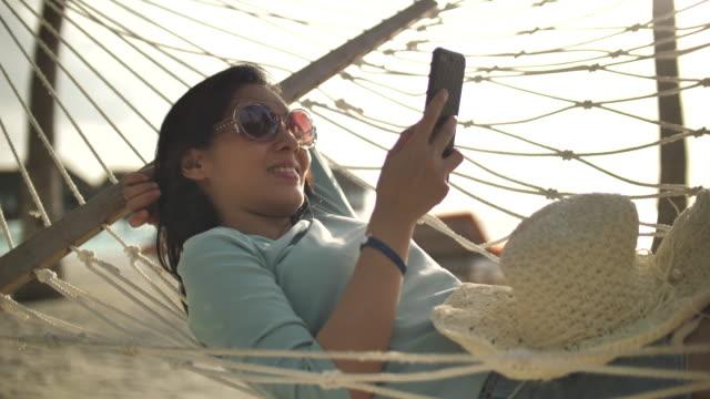 vidéos et rushes de femme asiatique utilisant le téléphone intelligent sur le hamac à la plage, vacances - royaume uni