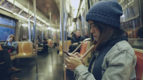 asian woman using smart phone on subway train. - subway train stock videos & royalty-free footage