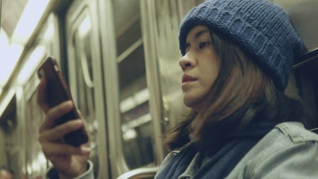 vídeos y material grabado en eventos de stock de mujer asiática utilizando teléfonos inteligentes en el metro. - coquetear
