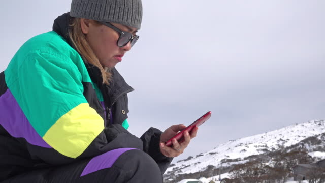 Asian woman using smart phone on the top of snow mountain.
