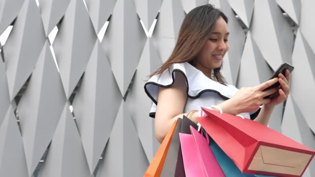 Asiatin mit Smartphone Handy mit Einkaufstüten