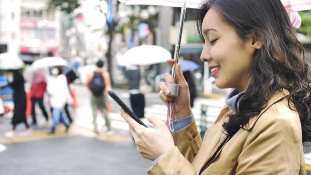 雨の中で携帯電話でスマートフォンのテキストメッセージを使用してアジアの女性 - 軽やか点の映像素材/bロール