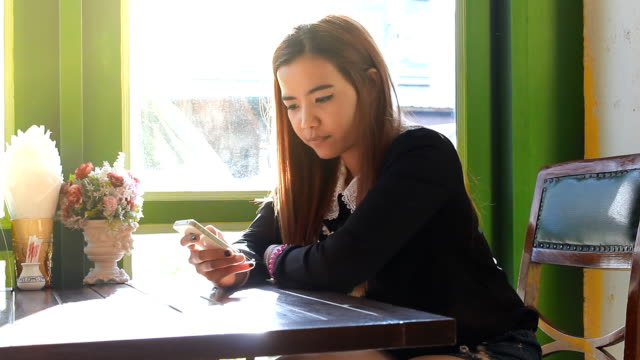 Asian woman using smart phone touchscreen in cafe drinking coffee