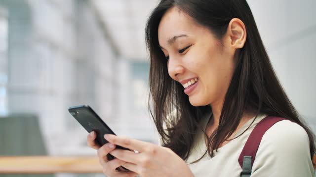 vídeos de stock, filmes e b-roll de mulher asiática usando telefone inteligente - portable information device
