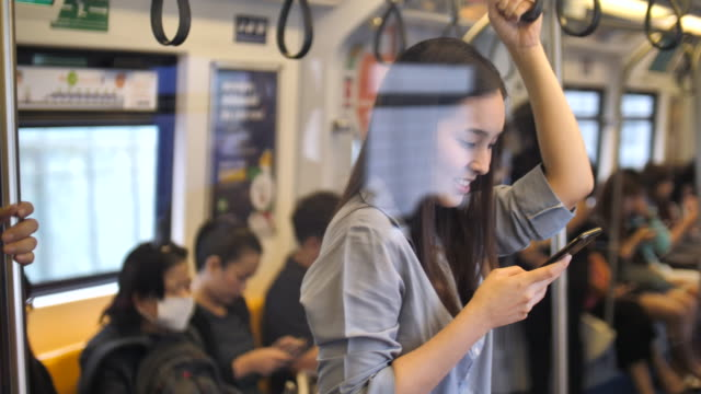 Asiatin mit Smartphone unterwegs im Sky-Train, Slow-motion