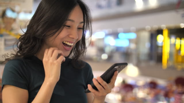asian woman using smart phone winning concept celebrating success - auction stock videos & royalty-free footage
