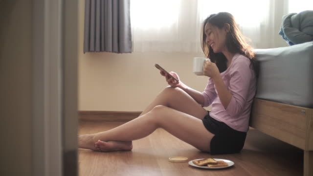 asian woman using smart phone with coffee cup and breakfast in bedroom - candid stock videos & royalty-free footage