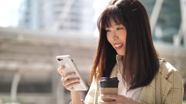 asiatische frau mit smartphone mit kaffeetasse - street name sign stock-videos und b-roll-filmmaterial