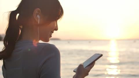 asiatisk kvinna använder smart telefon med hörlurar vid solnedgången på stranden för sin semester - motljus bildbanksvideor och videomaterial från bakom kulisserna