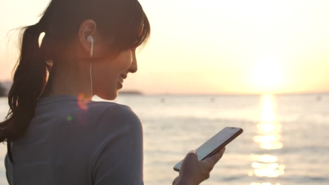 asian woman using smart phone with earphone at sunset on beach for her vacation - back lit stock videos & royalty-free footage