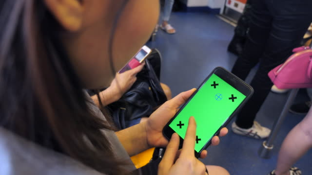 Asian woman using smart phone with Green screen on train, Slow motion
