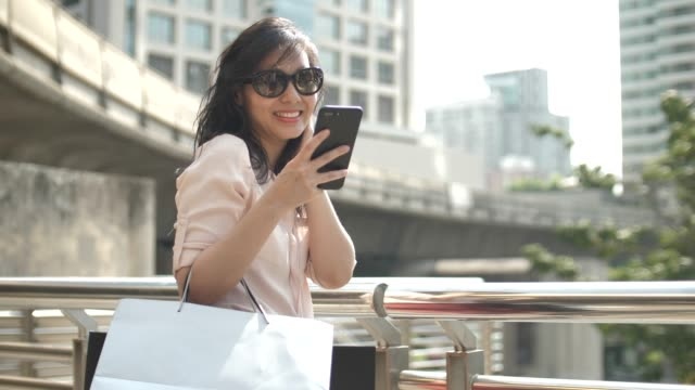 asian woman using smart phone with shopping bag - shopping bag stock videos & royalty-free footage