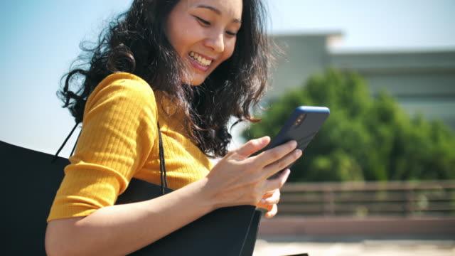 ショッピングバッグ付きスマートフォンを使用するアジアの女性 - バッグ点の映像素材/bロール
