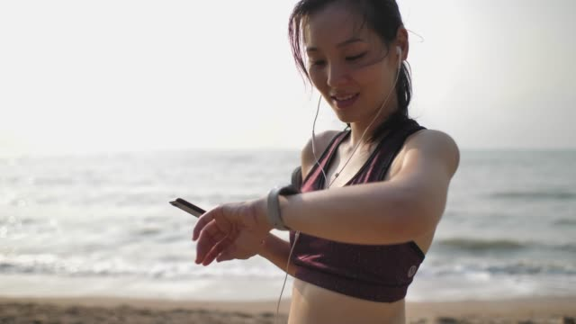 vídeos de stock e filmes b-roll de asian woman using smart watch and smart phone at beach - east asian ethnicity