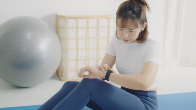 asian woman using smart watch before play yoga and exercise at home background.exercise for lose weight, increase flexibility and tighten the shape.4k slow motion. - slim stock videos & royalty-free footage