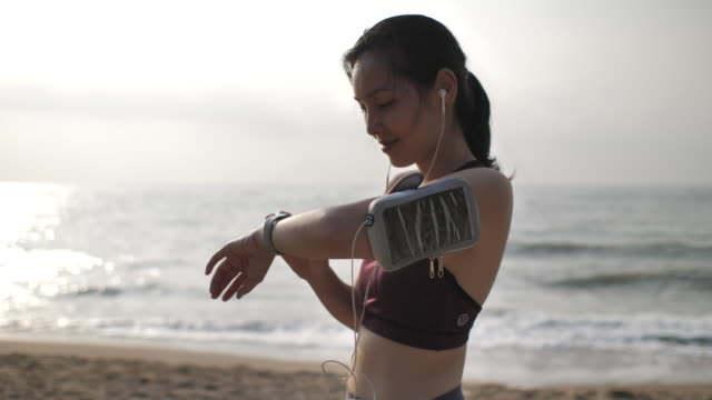 asian woman using smart watch for monitoring her running exercising on the beach - lifestyles stock videos & royalty-free footage