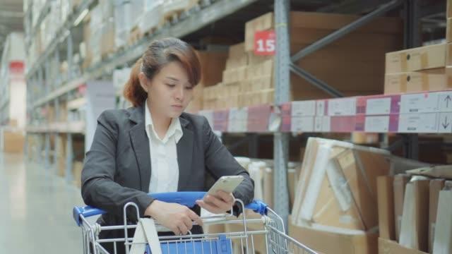 vídeos de stock, filmes e b-roll de mulher asiática usando o smartphone em armazém moderno - agenda eletrônica